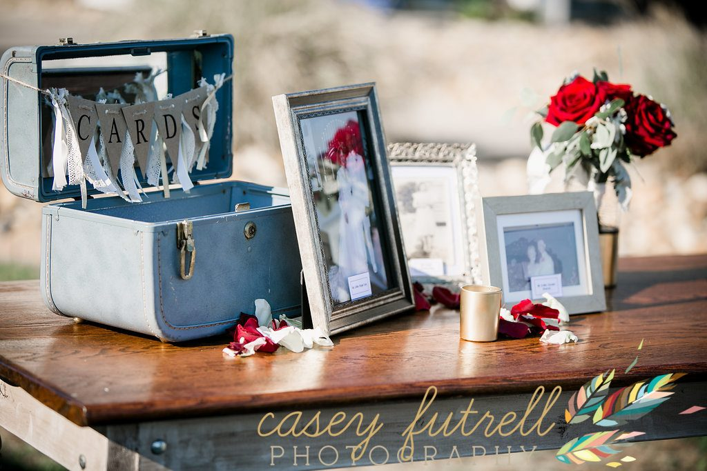 Boho themed reception, Suitcase card holder, wedding photos, antique table, oceanfront cocktail hour