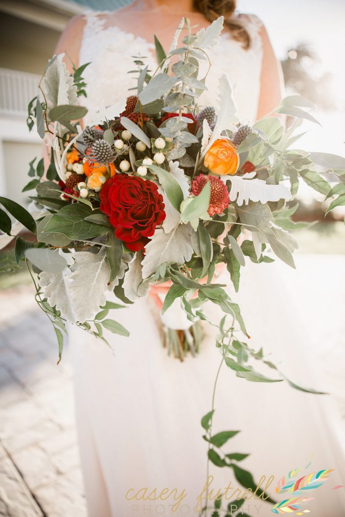 Wedding bouquet, red, lush greens, and pops of burnt orange