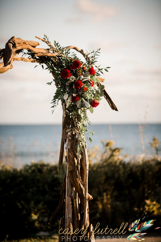 Red floral, driftwood arbor, oceanfront ceremony