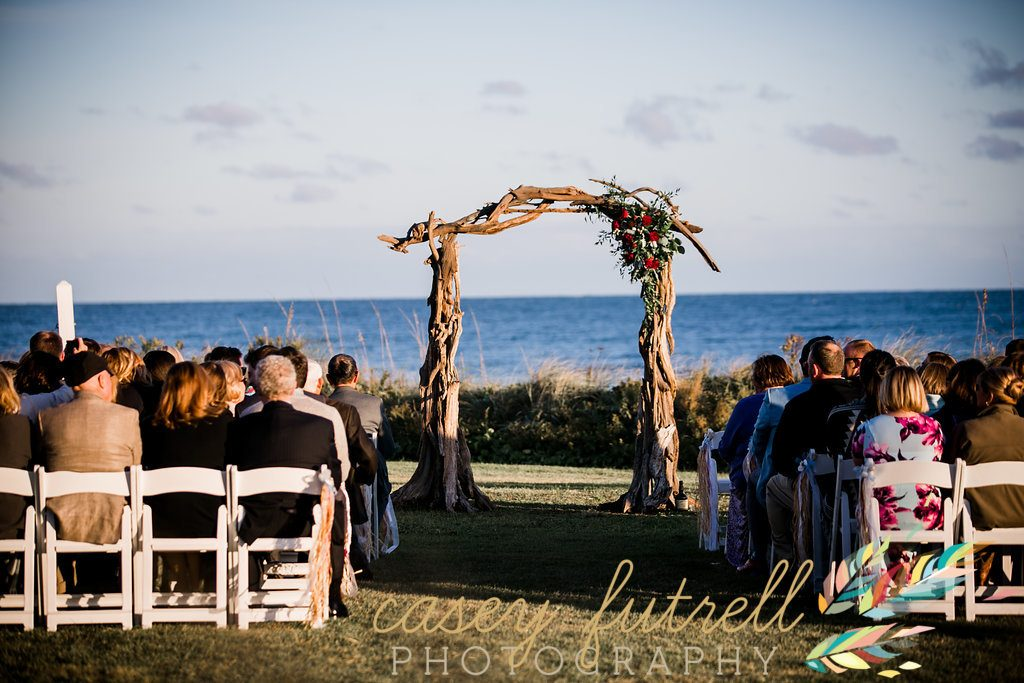 Driftwood arbor, red floral, oceanfront ceremony
